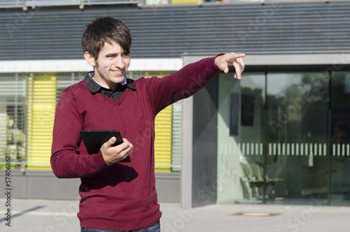 junger mann mit tablet zeigt in die ferne