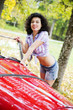 Woman in shirt posing on retro car side