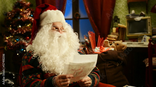 Portrait of Father Christmas sitting in chair reading letters