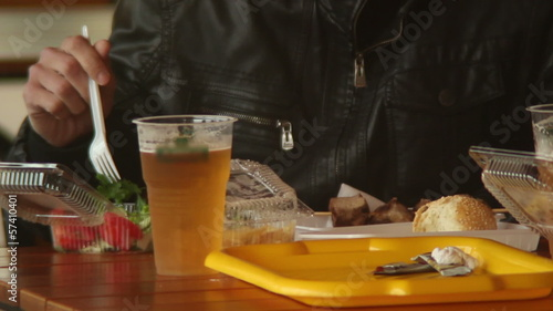 Man eating in fast food, drinking beer, plastic fork, burgers