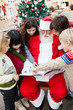 Santa Claus With Children Pointing At Book