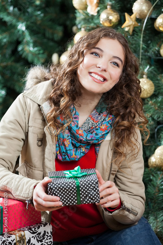 Woman With Presents Sitting Against Christmas Tree