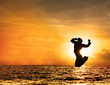 Silhouette of woman jumping at sunset with copy space