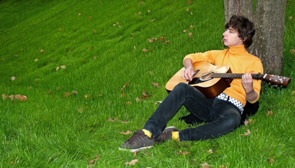 Teen with guitar on grass