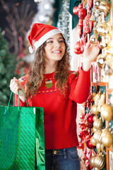 Woman Buying Christmas Ornaments In Store