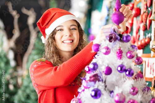 Female Owner Decorating Christmas Tree In Store