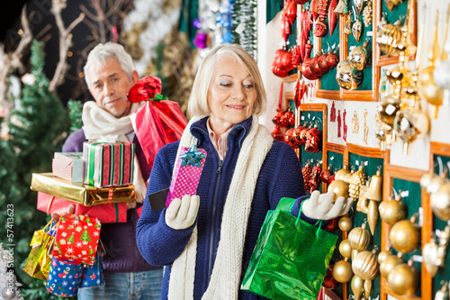 Senior Woman Shopping Christmas Ornaments At Store