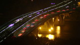 Night river bridge, cars leave traces yellow red light timelapse