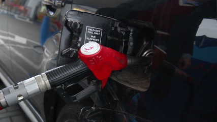 Fueling station service man glove pulls out pistol car gas