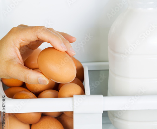 Female Hand picking one large egg from Refrigerator