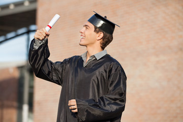 Man In Graduation Gown Looking At Certificate On Campus