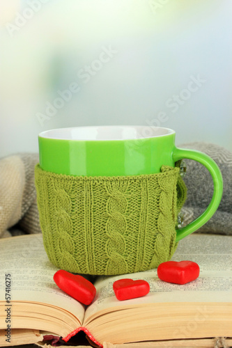 Cup with knitted thing on it and open book close up