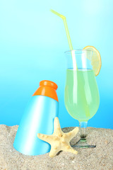 Beach cocktail and sunscreen in sand on blue background