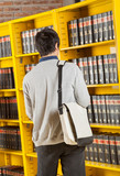 Student Carrying Bag While Standing In College Library