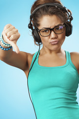 Young woman with headphones listening music . Thumbs down
