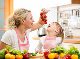 mother preparing dinner and feeding kid  tomato in kitchen