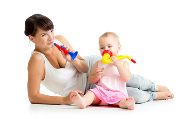 Mother and baby girl having fun with musical toys. Isolated on w