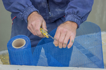 building worker cutting plastic grid with cutter
