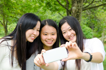Asian girls taking photo with handphone