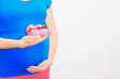 Pregnant woman holding pink baby shoes on her belly
