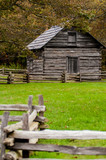 Beautiful Autumn scene showing rustic old log cabin surrounded b