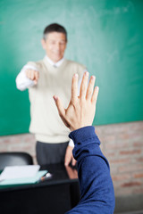 Student's Hand With Professor Pointing At Him In Classroom
