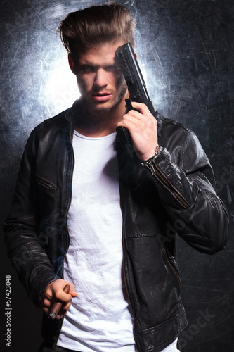young killer with a big gun is smoking cigar