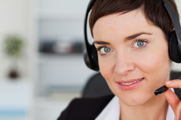 Close up of a cute secretary calling with a headset