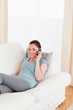 Good looking woman on the phone while lying on a sofa