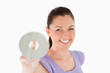 Beautiful woman holding a CD while standing
