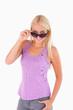 Charming woman peeking over her sunglasses