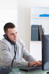 Businessman using his computer while talking on the phone