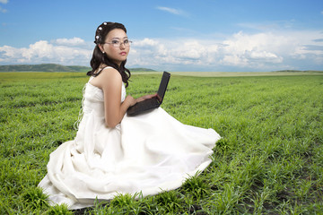 Girl in a long white dress, sitting on a grass with the computer