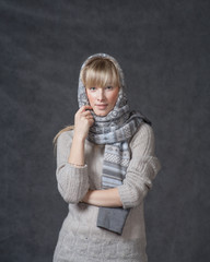 Portrait of woman on dark background wearing woolen accessories