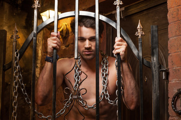 Sexy man standing behind metal gates.