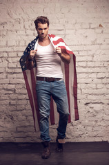 Sexy man using American flag like a cloak.