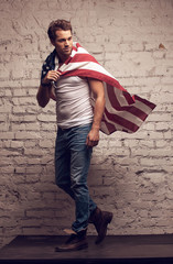 Handsome man walking using American flag like a cloak