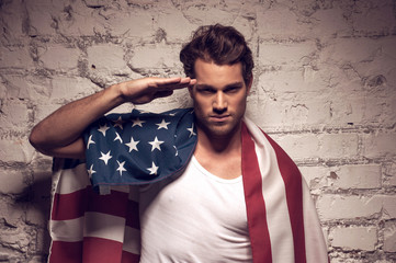 Young handsome man posing with American flag.