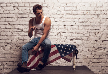 Brutal sexy man sitting on American flag.