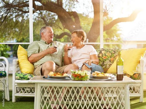 two seniors having dinner on patio. - 57426253