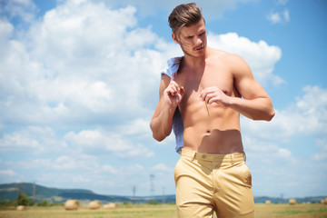 topless man outdoor looks down with straw in hand
