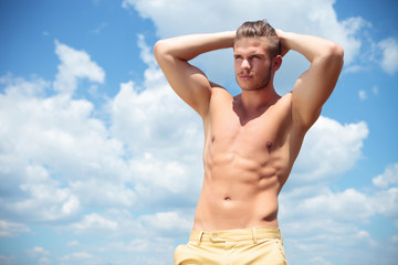 topless man outdoor with hands at back of head
