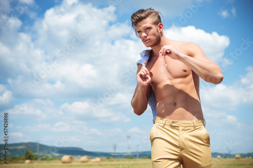 topless man outdoor walks with straw in hand