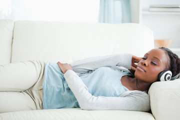 Woman listening to music while lying on couch