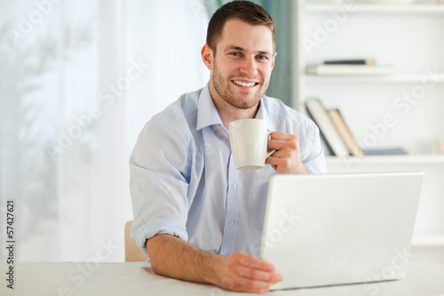 Smiling businessman having a cup of tea