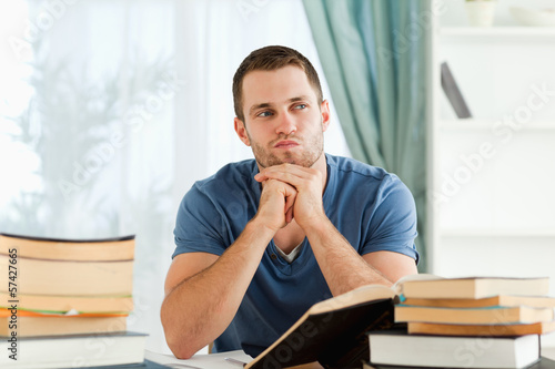 Student sitting at his desk in thoughts