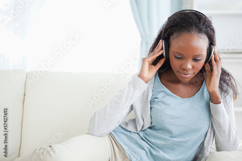 Fotobehang Muziek Woman sitting on couch listening to music