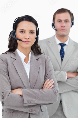 Call center agents with headsets and arms folded