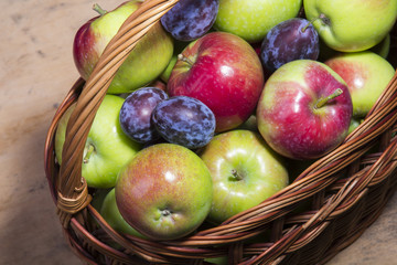 plums and apples in a wicker basket