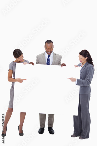 Businesspeople pointing and looking at blank sign